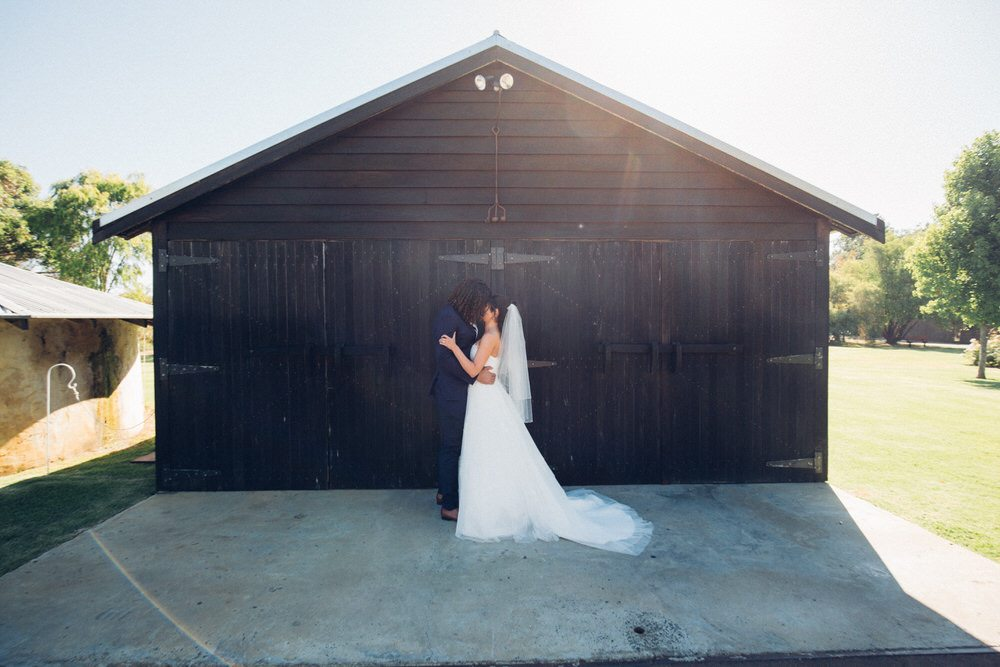 bride and groom kissing infront of rustic barn