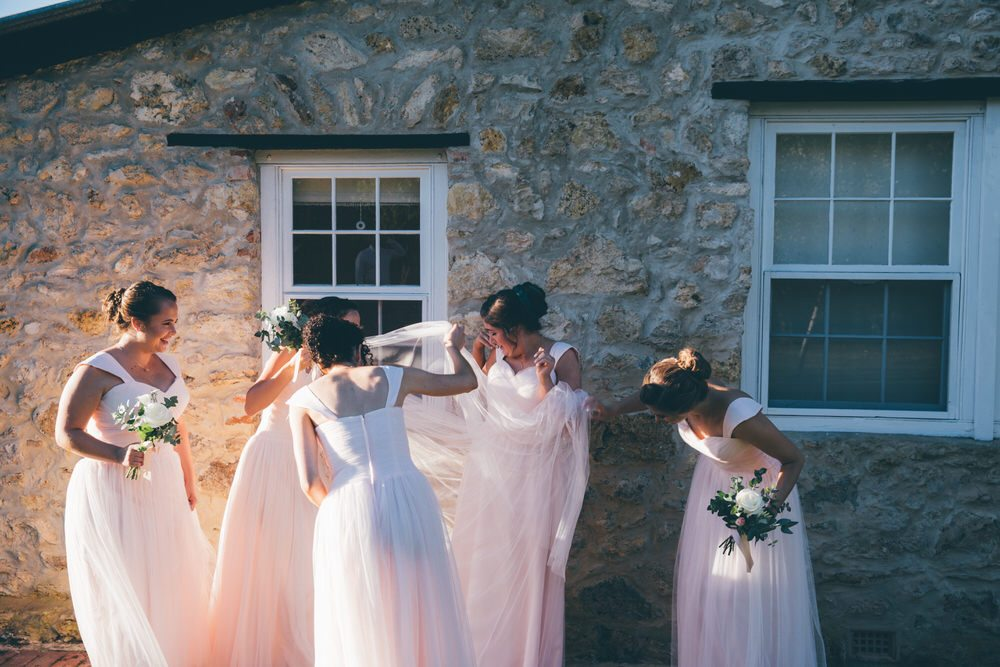 bridesmaids in front of stone cottage