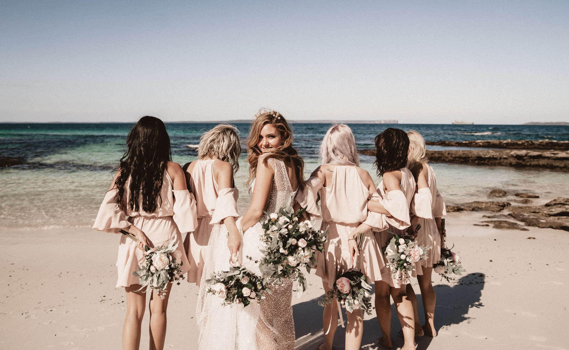 bride with bridesmaids at the beach
