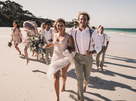 bride and groom walking on the sand